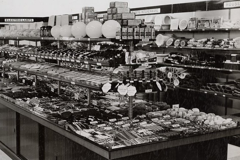 One of Woolworths' first self-service island counters.  Extension pieces have been used to display extra tiers of shelving above the main tabletop and lockable understocks cupboards (holding reserve stock to fill up with) were incorporated in the early designs.